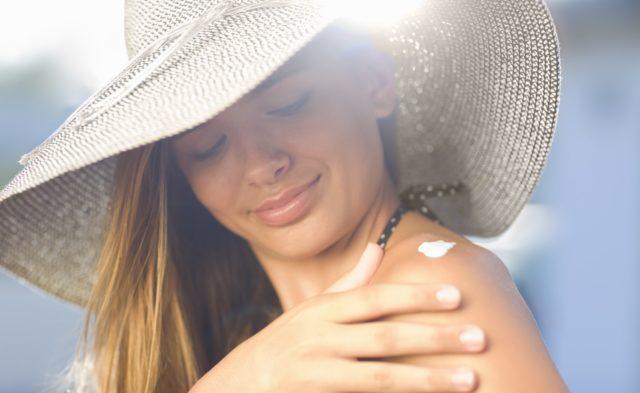 Woman applying sunscreen.