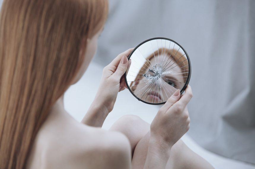 woman looking into broken mirror, mirror, broken, reflection