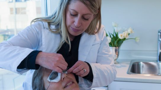 Doctor placing patches on eyes