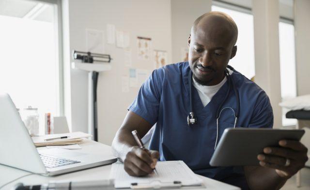 doctor writing on chart holding ipad