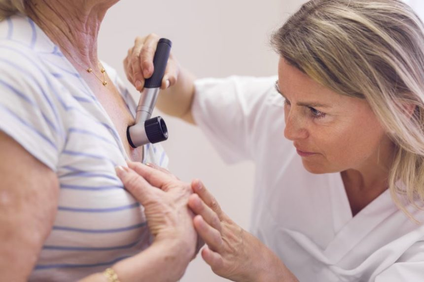 A dermatologist examining a woman's chest