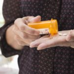A woman taking medication from a prescription bottle