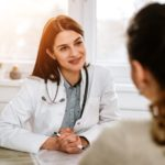 A physician speaking to her patient