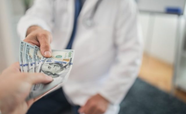 A patient handing a physician money