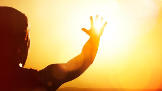 person reaching towards sun