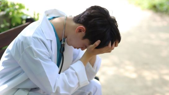 A doctor with his head in his hands