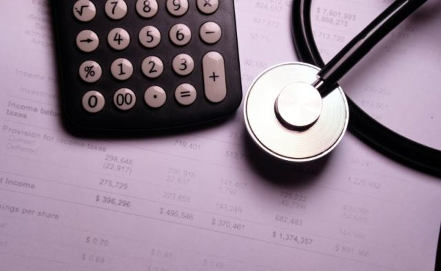 A stethoscope around medical bills and a calculator