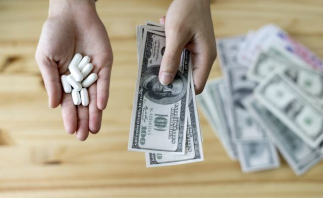 Someone holding pills and money