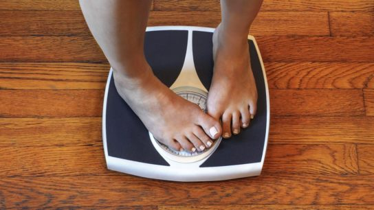 woman standing on scale covering weight