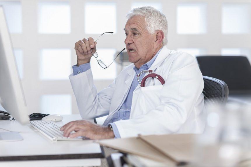 senior physician sitting at his desk.