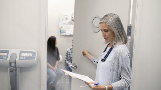 female doctor knocking on exam room door