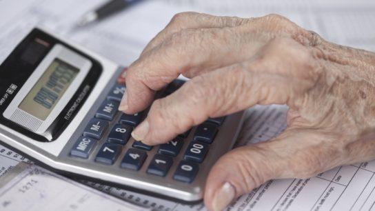 elderly woman hand with calculator