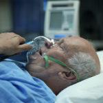 bald man in hospital bed receiving oxygen
