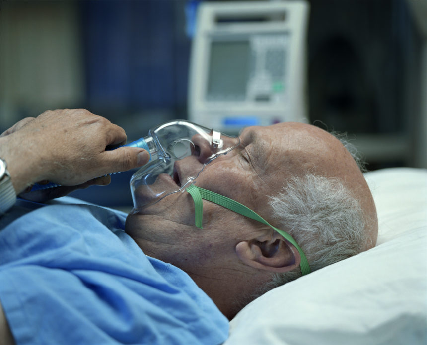 bald man in hospital bed receiving oxygen