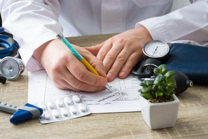 Doctor filling out prescription.